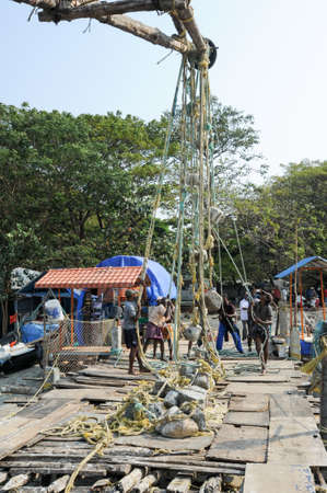 kochi: FORT KOCHI, INDIA - 16 JANUARY 2015: fishermen operate a Chinese fishing net based on ancient technology and traditional materials, ropes and stones at Fort Kochi, Kerala, India Editorial