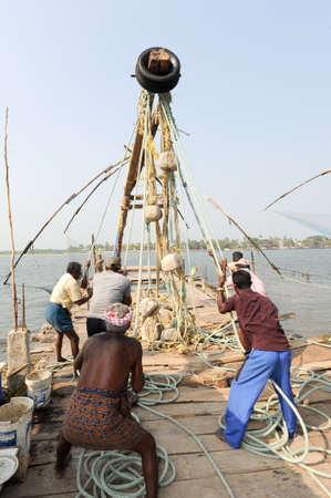 chinese fishing nets: FORT KOCHI, INDIA - 16 JANUARY 2015: fishermen operate a Chinese fishing net based on ancient technology and traditional materials, ropes and stones at Fort Kochi, Kerala, India Editorial