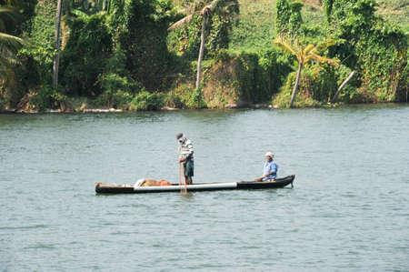 backwaters: Kollam, India - 20 January 2015: Fisherman fishing on a canoe near Kollam on Kerala backwaters, India