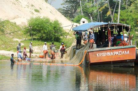 extending: Kollam, India - 20 January 2015: Fisherman extending a fishing net on a boat near Kollam on Kerala backwaters, India