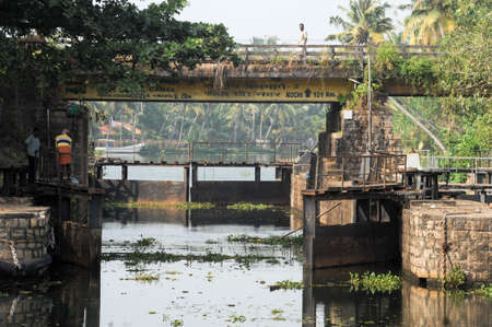 alappuzha: Kollam, India - 20 January 2015: People opening the gate for a boat passing a barrage on the way from Kollam to Alleppey on Kerala, India Editorial