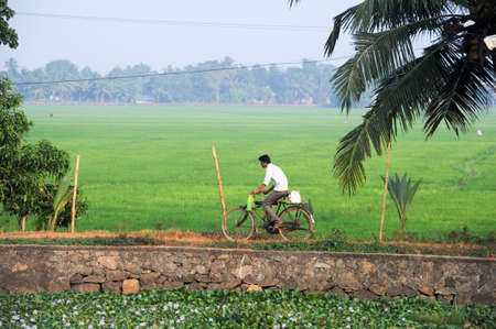 alappuzha: Kollam, India - 20 January 2015: Man traveling with his bike near Alleppey on Kerala backwaters, India