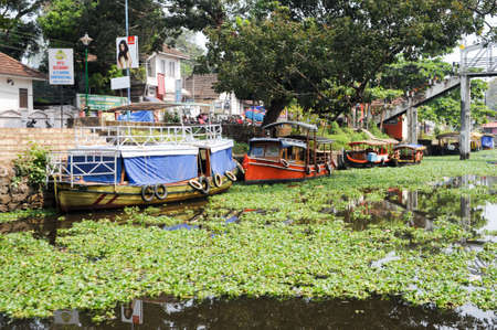 alappuzha: Boats cruising on a canal of Alleppey, India Editorial