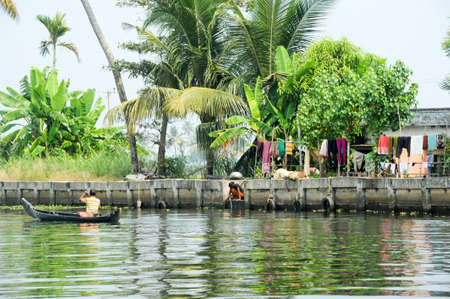 alappuzha: Alleppey, India - 21 January 2015: Man rowing a canoe on the backwaters of Alleppey, India