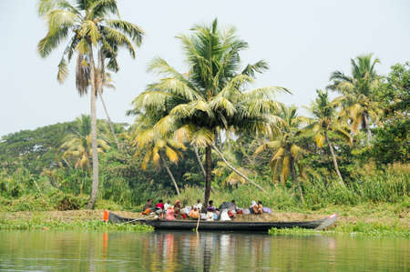 alappuzha: Alleppey, India - 21 January 2015: People resting on the shade of a palm tree at the backwaters of Alleppey, India Editorial