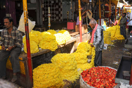 mysore: Mysore, India - 24 January 2015:  Indian vendor selling flowers to the customers in the Devaraja market at Mysore on India