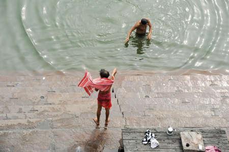 varanasi: Varanasi, India - 28 January 2015: Hindu pilgrims take a holy bath in the river ganges in Varanasi or Benares