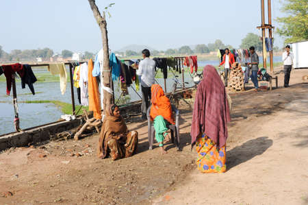 khajuraho: Khajuraho, India - 30 January 2015: People hanging clothes to dry after washing in front of lake Nanora on Khajuraho on India