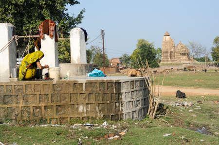 khajuraho: Khajuraho, India - 30 January 2015: Woman taking water from the waterhole in front of Khajuraho temple on India