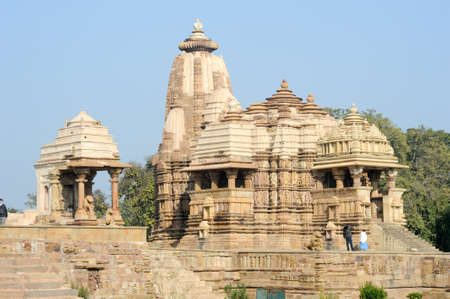 best guide: Khajuraho, India - 30 January 2015: People climb to the hindu temple on UNESCO World Heritage Site, Khajuraho Group of Monuments built between 950 and 1150