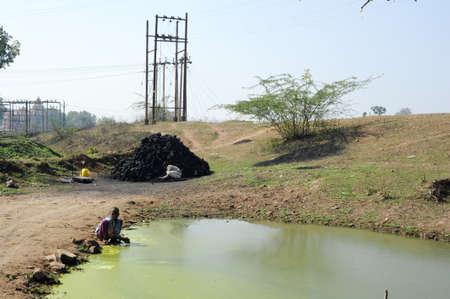 khajuraho: Khajuraho, India - 30 January 2015: Boy washing hands on a puddle near Khajuraho on India Stock Photo