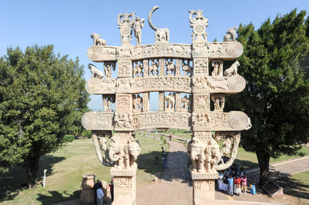 3rd century: Sanchi, india - 1 february 2015: People looking at the details of Carved decoration of the Northern gateway to the Great Stupa of Sanchi