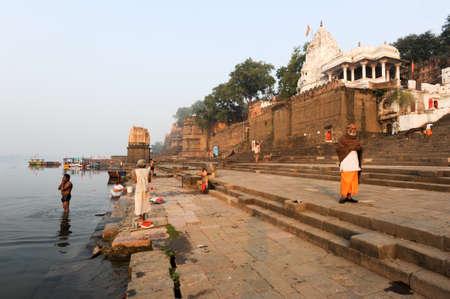hindus: Maheshwar, India - 03 de febrero 2015: personas que lavan a s� mismos en el r�o sagrado Narmada delante de Maheshwar palacio. Para los hind�es Narmada es uno de los 5 r�os sagrados de la India