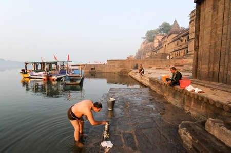 pooja: Maheshwar, India - 3 February 2015: Indian man performs morning pooja on sacred river Narmada ghats in Maheshwar, India. To Hindus Narmada is one of 5 holy rivers of India