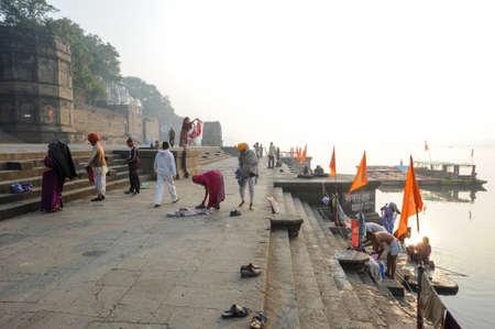 hindues: Maheshwar, India - 03 de febrero 2015: personas que lavan a s� mismos en el r�o sagrado Narmada delante de Maheshwar palacio. Para los hind�es Narmada es uno de los 5 r�os sagrados de la India