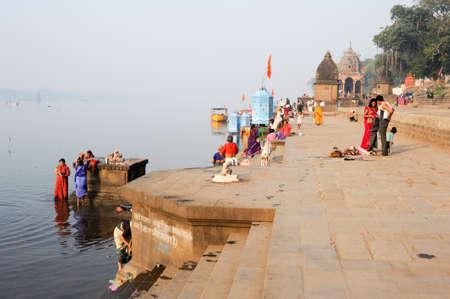 hindus: Maheshwar, India - 03 de febrero 2015: La gente lavando ropa en los r�os sagrados ghats Narmada. Para los hind�es Narmada es uno de los 5 r�os sagrados de la India Editorial