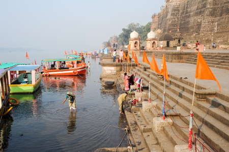hindus: Maheshwar, India - 3 February 2015: People washing clothes on sacred river Narmada ghats. To Hindus Narmada is one of 5 holy rivers of India