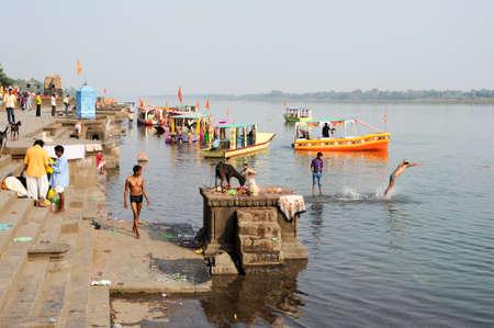 hindues: Maheshwar, India - 03 de febrero 2015: La gente lavando ropa en los r�os sagrados ghats Narmada. Para los hind�es Narmada es uno de los 5 r�os sagrados de la India Editorial