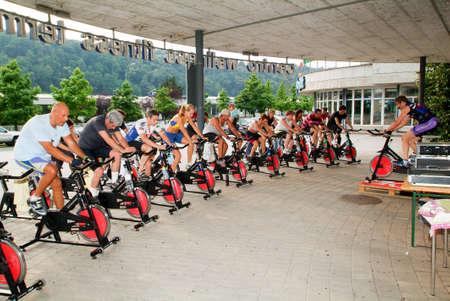 Lugano, Suiza -17 junio de 2005: La gente pedaleando durante una clase de spinning