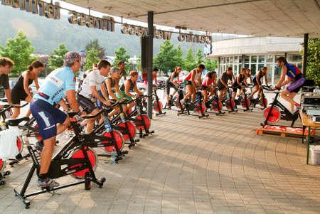 Lugano, Suiza -24 junio de 2005: La gente pedaleando durante una clase de spinning