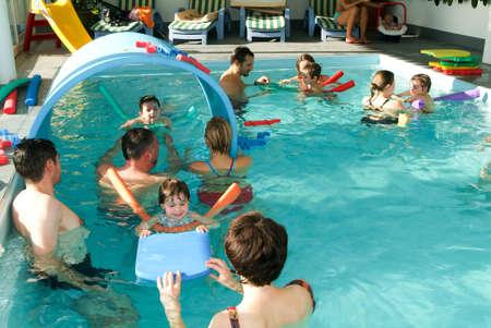 natacion: Lugano, Suiza - 12 de noviembre 2004: babys adorables disfrutar nadando en una piscina con con sus familiares, clase el desarrollo temprano de los beb�s que ense�an a los ni�os a nadar y bucear Editorial