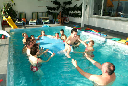 12 class: Lugano, Switzerland - 12 November 2004: Adorable babys enjoying swimming in a pool with with their relatives, early development class for infants teaching children to swim and dive