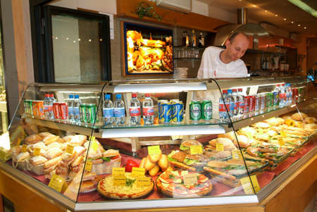 Locarno, Switzerland: 6 april 2010: Worker selling sandwich on a restaurant of Locarno on Switzerland