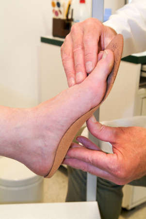 insoles: Doctor preparing orthopedic insoles for a patient on his studio