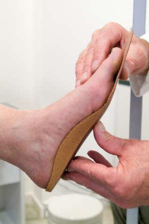 彼のスタジオの上に患者を整形外科のインソールを準備、医師