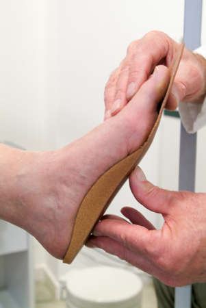 suo: Medico che prepara plantari ortopedici per un paziente su sua bottega Archivio Fotografico