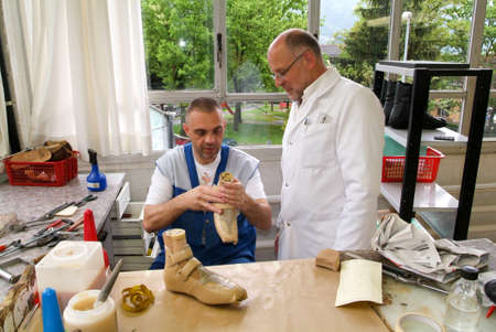 inset: Locarno, Switzerland: 4 May 2010: Doctor and worker preparing orthopedic insoles for a patient on them workshop