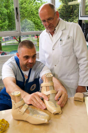Locarno, Switzerland: 4 May 2010: Doctor and worker preparing orthopedic insoles for a patient on them workshop