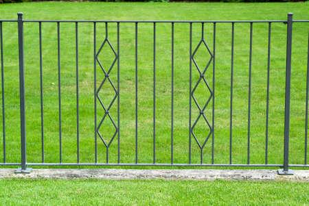 Black wrought iron gate in a beautiful green garden