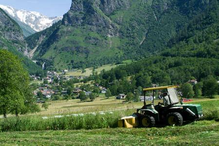 framer: Olivone, Switzerland - 25 June 2010: Framer on his tractor cutting the grass on a field near Olivone on the Swiss alps