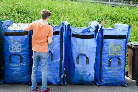 botellas pet: Lugano, Suiza - 09 de mayo 2015: Hombre arrojar botellas PET en el contenedor de un centro de reciclaje