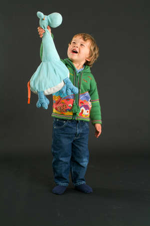 stuffed animal: Young boy posing with a stuffed animal on a black background Stock Photo