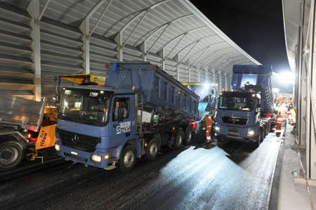 asphalting: Bissone Switzerland  11 September 2007: Workers and vehicles during the asphalting of the highway by night at Bissone on Switzerland