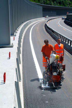 infra construction: Bissone Switzerland  20 June 2011: Machine eject and worker on road and traffic sign painting