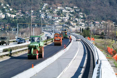 asphalting: Bissone Switzerland  8 March 2007: Workers and vehicles during the asphalting of the highway at Bissone on Switzerland Editorial