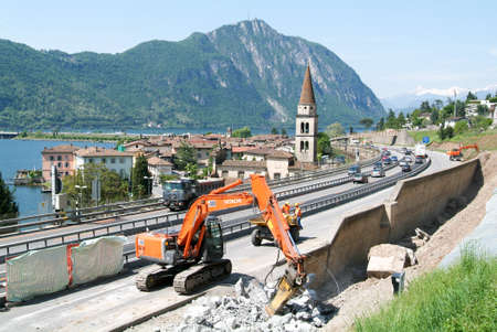 breaking up: Bissone Switzerland  28 May 2008: Workers breaking up a wall with a Hydraulic digger on a highway at Bissone on Switzerland