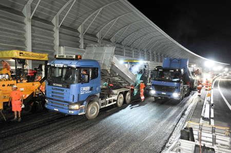 11 september: Bissone Suiza 11 septiembre de 2007: Los trabajadores y los veh�culos durante el asfaltado de la carretera por la noche en Bissone en Suiza