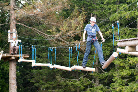 elated: Mount Pilatus, Switzerland - 23 August 2006: Visitors in adventure park clambering with ropes wear protective helmets