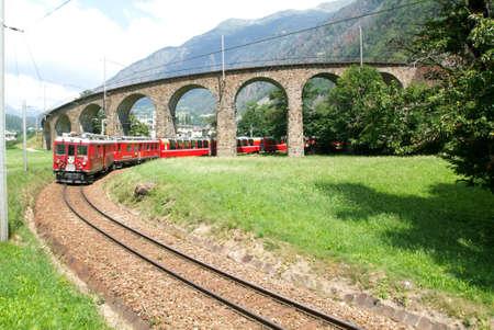 treno espresso: Bernina Express Train presso il viadotto circolare di Brusio sulle alpi svizzere. Patrimonio dell'Unesco