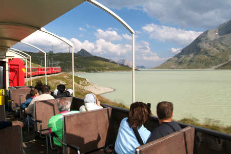 treno espresso: Bernina Express, Svizzera - 21 Luglio 2015: La gente che si siede sul Bernina Express treno e ammirando la vista panoramica sulle Alpi svizzere