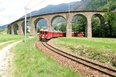 rack mount: Bernina Express Train at the circular Viaduct of Brusio on the Swiss alps. Unesco world heritage site Editorial