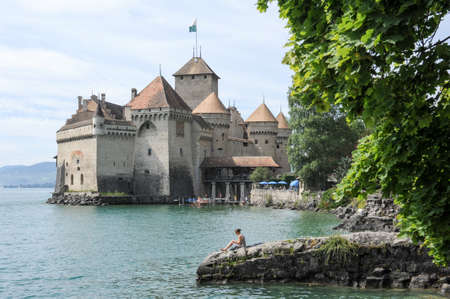 montreux: Montreux, Switzerland - 16 July 2011: woman reading a book on the lakeside in front of the castle of Chillon in Montreux, Switzerland