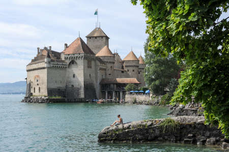 chillon: Montreux, Switzerland - 16 July 2011: woman reading a book on the lakeside in front of the castle of Chillon in Montreux, Switzerland
