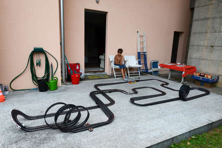 slot car track: Lugano, Switzerland - 26 July 2015: Boy playing with a Car Racing Track on the garden