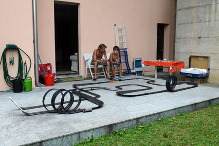 slot car track: Lugano, Switzerland - 26 July 2015: Father and son playing with a Car Racing Track on the garden