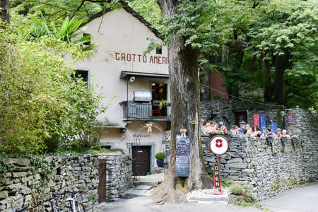 Ponte Brolla, Switzerland - 30 July 2015: People eating on a Grotto, a typical restaurant on the italian part of Switzerland at Ponte Brolla on Maggia valley